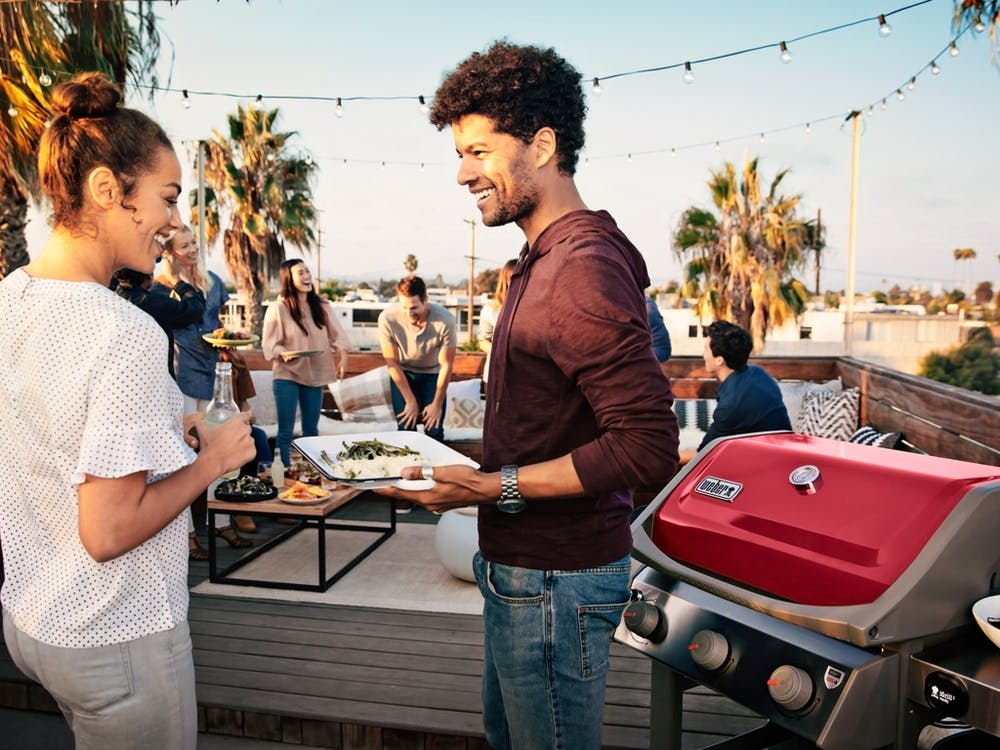 People at a party enjoying meat cooked from a Spirit II Gas Grill