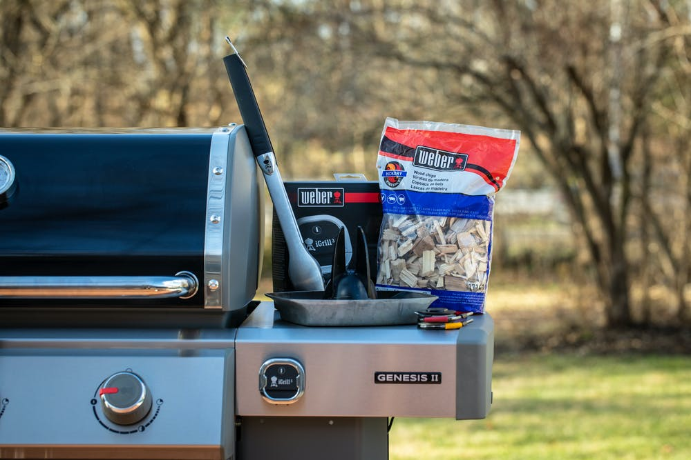 Weber Grills tongs, deluxe poultry roaster pan, iGrill thermometer, and hickory chips on the Weber Genesis II gas grill